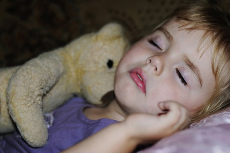 sleeps: small beautiful girl sleeps with plush teddy bear