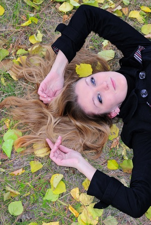 The young beautiful girl lies on a green grass with yellow leaves on a back photo