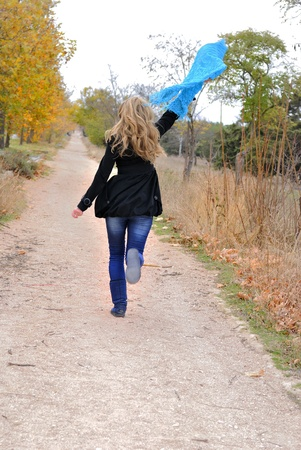 The young beautiful girl runs in autumn wood with a scarf in hands photo