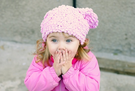 Portrait of the small beautiful surprised girl with in a pink cap
