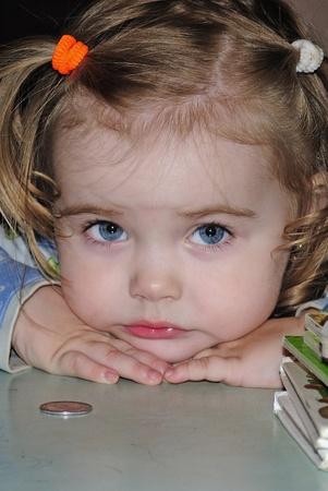 small beautiful girl looks at kopeck Stock Photo
