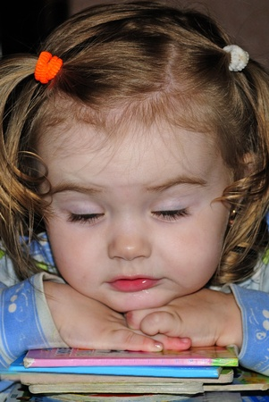 small beautiful girl fell asleep on book