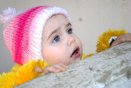 parapet: The small surprised beautiful girl looks out behind a parapet  Stock Photo