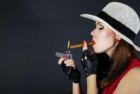 younger beautiful girl with red pomade with cigar in black hat Stock Photo - 12731910