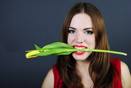 making look younger beautiful bright girl with red pomade keeps teeth a tulip  photo