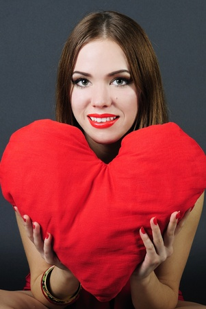 making look younger beautiful bright girl with red heart in hand photo