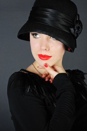 madam: making look younger beautiful girl with red pomade in black cloth and hat