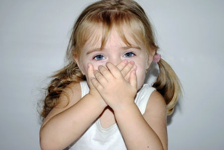 small beautiful girl has closed mouth a hand Stock Photo