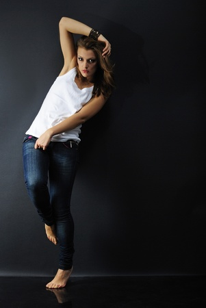 harming: beautiful girl model in white tanktop and jeans on dark background