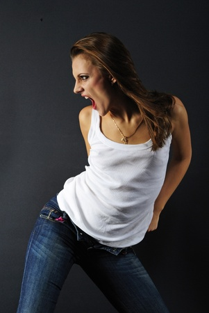 bosom: beautiful girl model in white tanktop and jeans on dark background