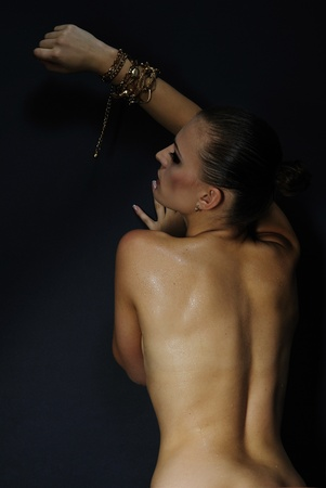 nacked: beautiful girl model with wet body on dark background  Stock Photo