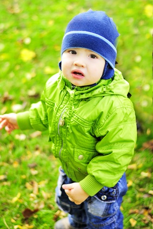 The small beautiful boy walks on a green glade  photo