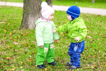Two small children sit on a green clearing with yellow leaves  Stock Photo - 13493100