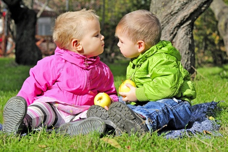 Small children kiss on a green clearing in the autumn