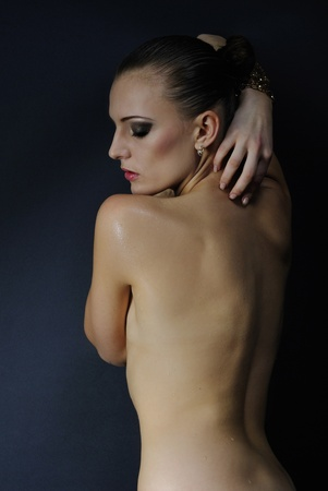 perspiration: beautiful girl model with wet body on dark background