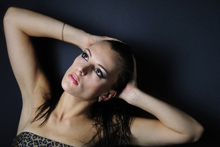 beautiful girl brunette model in leopard topic and jeans on black background