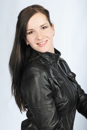 portrait of the young beautiful girl of the brunette with spectacles in black leather jacket