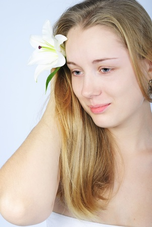 nacked: making look younger beautiful girl blonde with white lily Stock Photo