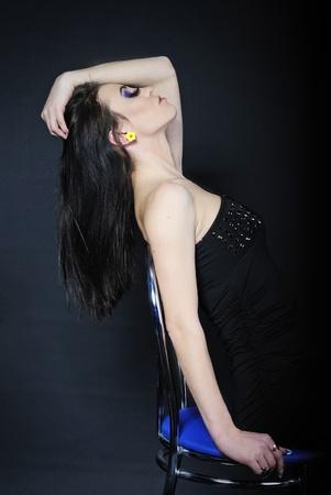 harming: Beautiful stylish girl brunette with additional long lash on dark background