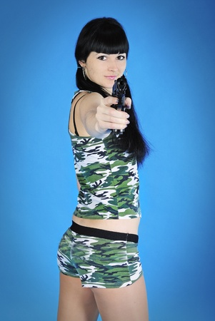 beautiful girl brunette with long hair with weapon on turn blue background  photo