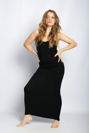ladylike: younger beautiful girl in black long gown with long hair on white background