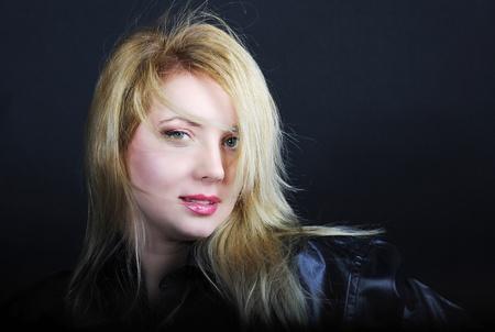 Beautiful girl blonde in black shirt on black background
