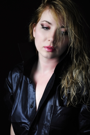 briliance: Beautiful girl blonde in black shirt on black background with wet hair and bracelet  Stock Photo