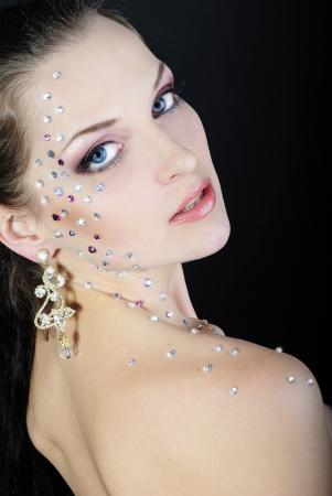 beautiful girl fashionable on dark background with bright diamond photo