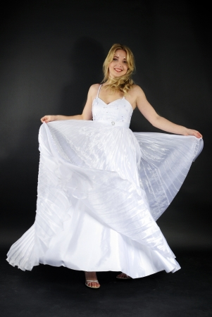 beautiful blonde in white gown on gray background photo