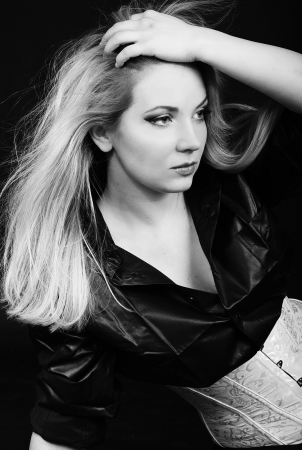 Beautiful girl blonde in white and black shirt on black background