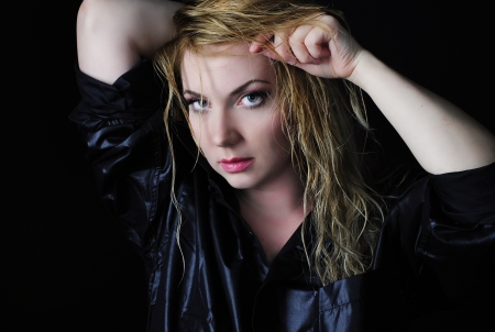 Beautiful girl blonde in black shirt on black background with wet hair and bracelet  Stock Photo