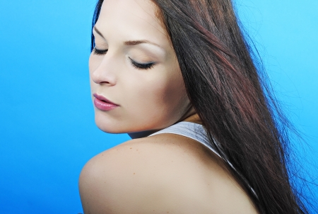 downwards: Beautiful girl brunette with long hair on turn blue background looks downwards