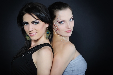 Two beautiful stylish fashionable girls to models with diamond and long lash on dark background photo