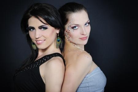 Two beautiful stylish fashionable girls to models with diamond and long lash on dark background photo
