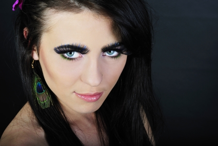 Beautiful stylish girl brunette with additional long lash on dark background photo