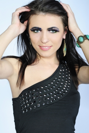 Beautiful stylish girl brunette with additional long lash on white background in black gown  photo