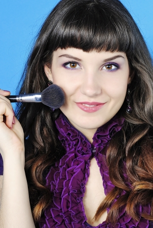 briliance: Beautiful girl visagiste with tassel for make-up with long hair on blue background  Stock Photo