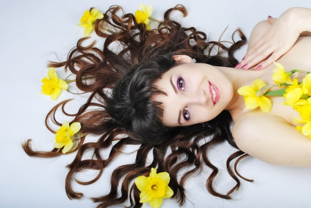 briliance: Beautiful smiling girl with long curly hair on blue background with yellow colour in hair Stock Photo