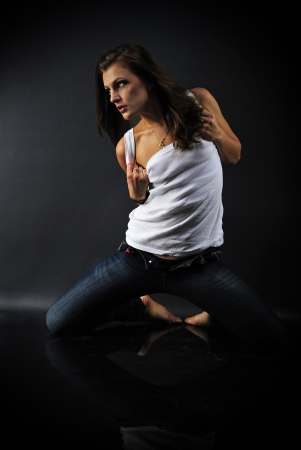 beautiful girl model in white tanktop and jeans on dark background