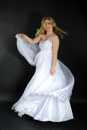 beautiful blonde in white gown on gray background Stock Photo