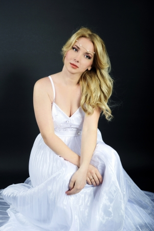 ccedil: beautiful blonde in white gown on gray background Stock Photo