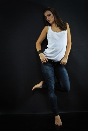 tanktop: beautiful girl model in white tanktop and jeans on dark background