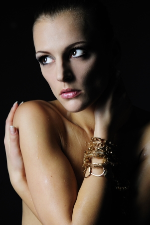 harming: beautiful girl model with wet body on dark background  Stock Photo
