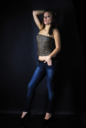 harming: beautiful girl brunette model in leopard topic and jeans on black background
