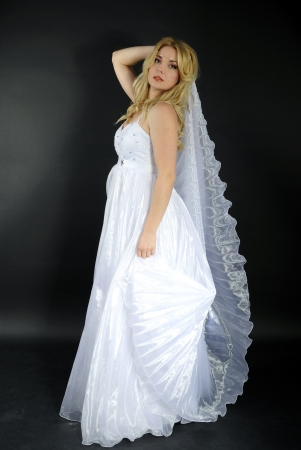 atilde: beautiful blonde in white gown on gray background Stock Photo