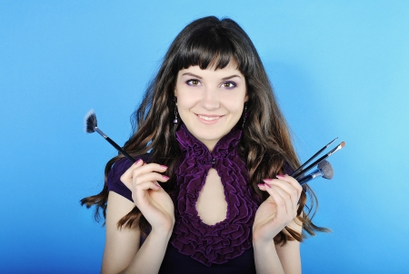 visagiste: Beautiful girl visagiste with tassel for make-up with long hair on blue background  Stock Photo