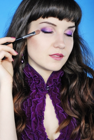 briliance: Beautiful girl visagiste with tassel for make-up with long hair on blue background