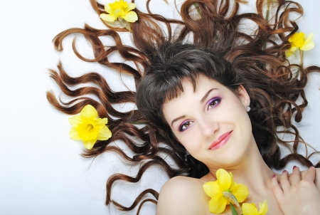 briliance: Beautiful smiling girl with long curly hair on blue background with yellow colour in hair