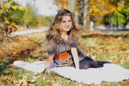 The young beautiful girl in autumn wood sits on a white plaid Stock Photo - 16788214