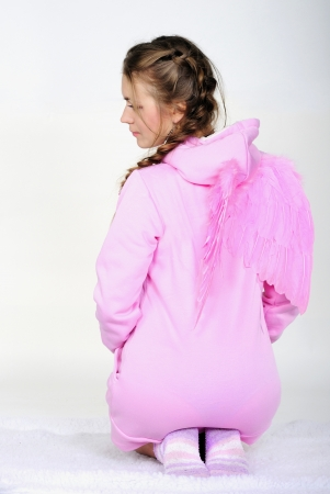 The young beautiful girl in a pink jacket with wings on a white background Stock Photo - 16784102